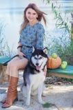 La muchacha y su perro esquimal del perro se está sentando cerca del río Fotos de archivo libres de regalías