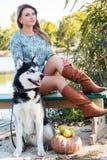 La muchacha y su perro esquimal del perro se está sentando cerca del río Imagen de archivo libre de regalías