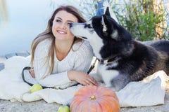 La muchacha y su perro fornido está mintiendo cerca del río Imagen de archivo libre de regalías