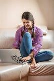 La muchacha y un ordenador portátil en el sofá Foto de archivo
