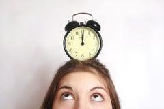 La muchacha y un reloj de alarma. Fotografía de archivo