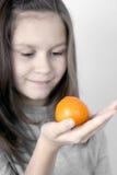 La muchacha y una mandarina Fotos de archivo