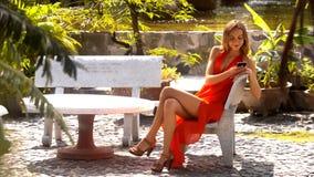 La muchacha zanquilarga se sienta con el teléfono en parque ilustrado