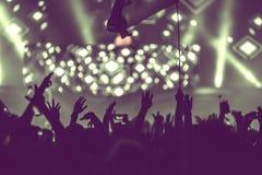 La muchedumbre de audiencia con las manos aumentó en un festival de música Imagenes de archivo