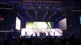 La muchedumbre de gente salta con los brazos aumentados cerca de etapa con los proyectores por la tarde metrajes