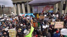 La muchedumbre de manifestantes va Individuo alto en un traje verde en los zancos con la bandera almacen de video