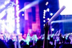 La muchedumbre de manos para arriba brilla intensamente las luces de la etapa del concierto del palillo Foto de archivo