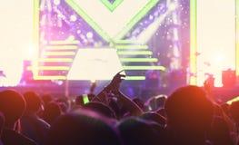 La muchedumbre de manos sube luces de la etapa del concierto Imagen de archivo