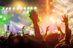 La muchedumbre de manos sube luces de la etapa del concierto Fotografía de archivo