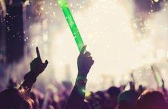 La muchedumbre de manos sube luces de la etapa del concierto Imagenes de archivo