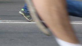 La muchedumbre está corriendo en el asfalto en zapatillas deportivas de izquierda a derecha almacen de video