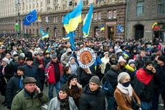 La muchedumbre global de hombres y de mujeres con diversas banderas y los bunners antigubernamentales que caminan abajo de la call Foto de archivo