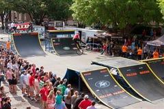 La muchedumbre mira BMX favorable realizar trucos de la rampa en la competencia de Atenas Foto de archivo libre de regalías