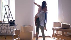 La mudanza feliz al nuevo apartamento, los pares alegres se está divirtiendo y el hombre está llevando a la hembra encendido detr almacen de video