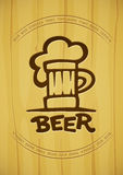 La muestra de la taza con la cerveza contornea la silueta en fondo de madera Fotos de archivo libres de regalías