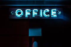 La muestra de neón azul de la oficina brilla intensamente en la noche Imagen de archivo