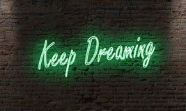 la muestra de neón de la letra con la cita guarda el soñar en una pared de ladrillo adentro Fotografía de archivo