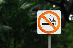 La muestra de no fumadores con el polo de acero está en un parque público Fotos de archivo libres de regalías
