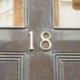 La muestra del número de casa 18 en negro pintó la puerta Fotos de archivo libres de regalías