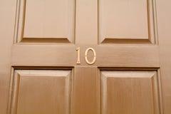 La muestra del número de casa 10 en puerta de madera pintó marrón Fotografía de archivo