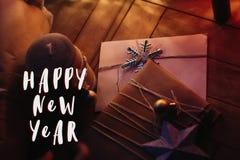 La muestra del texto de la Feliz Año Nuevo en arte rústico de la Navidad presenta con Fotos de archivo