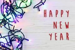 La muestra del texto de la Feliz Año Nuevo en el marco de la Navidad de la guirnalda se enciende C Fotografía de archivo libre de regalías