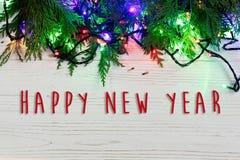 La muestra del texto de la Feliz Año Nuevo en el marco de la Navidad de la guirnalda se enciende encendido Fotografía de archivo libre de regalías