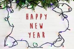 La muestra del texto de la Feliz Año Nuevo en el marco de la Navidad de la guirnalda se enciende encendido Fotos de archivo libres de regalías