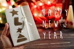 La muestra del texto de la Feliz Año Nuevo a mano que llevaba a cabo la Navidad envolvió pres Fotos de archivo