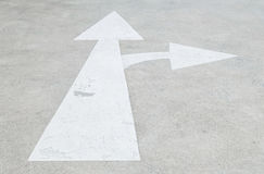 La muestra pintada blanco de la flecha del primer en fondo del piso de la calle del cemento, firma adentro va derecho y dirección Fotos de archivo