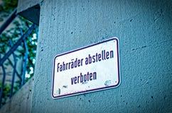 La muestra y la prohibición firman con la advertencia en alemán Pare las bicicletas prohibidas en bicis inglesas del estacionamie Fotos de archivo libres de regalías