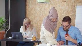 La mujer árabe está hablando con el hombre del colega en la oficina, corrigiendo su informe almacen de video