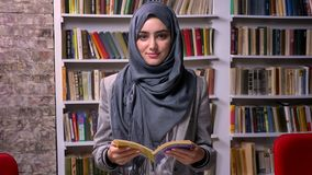 La mujer árabe hermosa en hijab gris todavía se está colocando y está sosteniendo el libro, galce confiado serio en la cámara, bi almacen de video