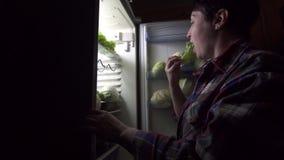 La mujer 40 años durante una dieta mira en el refrigerador metrajes