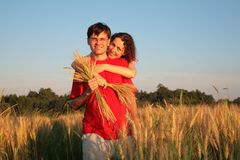 La mujer abraza al hombre detrás en campo de trigo Imagen de archivo libre de regalías