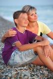 La mujer abraza al muchacho sonriente en la playa por la tarde Foto de archivo libre de regalías