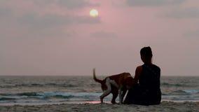 La mujer abraza su perro en la puesta del sol