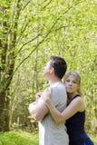 La mujer abraza a un hombre que se esté colocando con ella de nuevo a ella El concepto de problemas de la familia, perdón fotografía de archivo libre de regalías