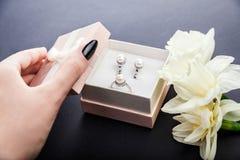 La mujer abre la caja de regalo con joyería de la perla Sistema de pendientes y del anillo con las flores como presente para el d Fotografía de archivo