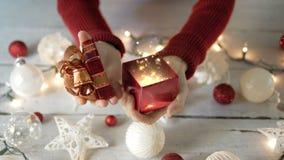 La mujer abre la caja de regalo con las luces del oro mágicas con la decoración de la Navidad almacen de metraje de vídeo