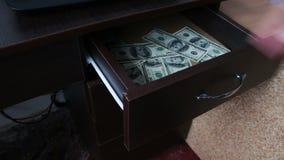 La mujer abre el cajón y hay muchas cuentas del ciento-dólar metrajes