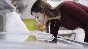 La mujer abre el refrigerador, búsquedas para la comida congelada y lo cierra en supermercado almacen de video