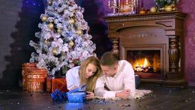 La mujer abre el regalo de la Navidad en la Nochebuena metrajes