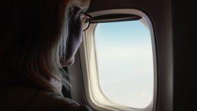 La mujer abre la cortina de la ventana en el avión Concepto del viaje que comienza metrajes