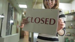 La mujer abre la tienda y letrero el mover de un tirón con la muestra cerrada metrajes