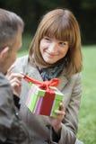 La mujer abre un rectángulo de regalo Imágenes de archivo libres de regalías