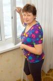 La mujer abre una ventana Fotografía de archivo libre de regalías