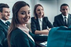 La mujer acertada joven se está sentando en la reunión de negocios con los colegas en la sala de conferencias Foto de archivo