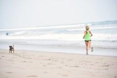La mujer activa abajo de la playa con su perro Fotos de archivo