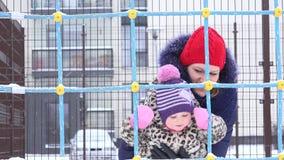 La mujer activa con el bebé disfruta de la ventisca de la caída de la nieve en yarda de la casa 4K almacen de metraje de vídeo